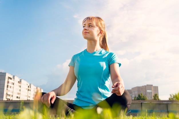 Mooie aantrekkelijke jonge vrouw die zich uitstrekt in het park. zomer tijd. gezondheidsconcept. geschiktheidsconcept. blonde atleet