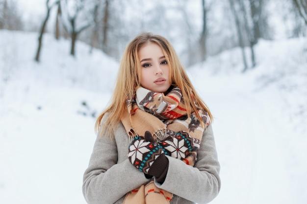 Mooie aantrekkelijke jonge vrouw in een modieuze grijze jas in vintage gebreide wanten met een stijlvolle beige sjaal met een patroon rust in een besneeuwd park op een koude winterdag. charmante meisjesblonde.