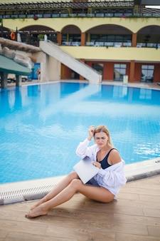 Mooie aantrekkelijke jonge vrouw zit in de buurt van een groot zwembad en werkt op een laptop. werken op afstand tijdens de vakantie.