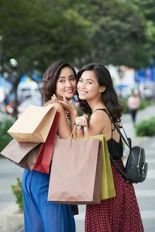 Mooie aantrekkelijke jonge vrouwen die langs de straat lopen met veel boodschappentassen die omkeren en...
