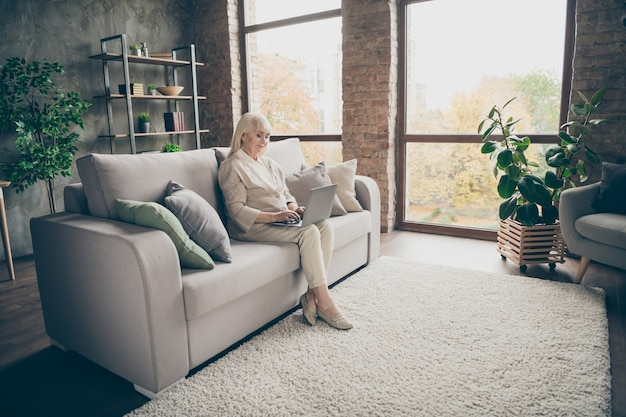 Mooie aantrekkelijke rustige vreedzame gerichte vriendelijke bekwame grijsharige dame zittend op een divan browsen informatie online arts raadpleging bezoek industriële baksteen loft moderne stijl interieur huis woonkamer