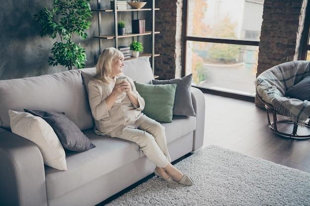 Mooie aantrekkelijke vrolijke dromerige soort grijsharige blonde oma van middelbare leeftijd zittend op een divan rusten drinken kruidenthee op industriële loft moderne stijl interieur huis appartement plat