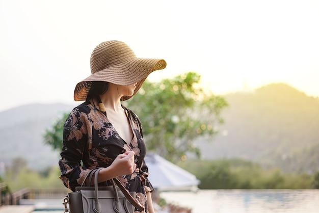 Mooie aantrekkelijke vrouw bij het zwemmende terras met overmaatse hoed voor haar ogen