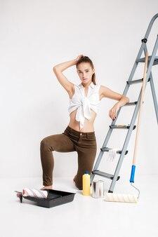 Mooie aantrekkelijke vrouw die een muur in haar huis schildert