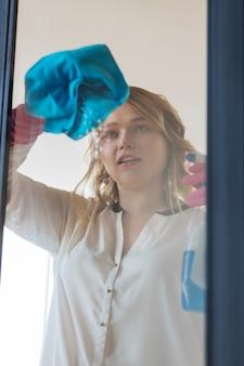 Mooie aardige vrouw die naar het raam kijkt terwijl ze het schoonmaakt