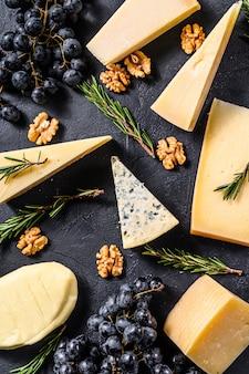 Mooie achtergrond met verschillende soorten heerlijke kaas, walnoten en druiven. bovenaanzicht