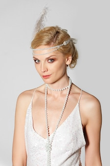 Mooie actrice in parelwitte retro jurk en pluim in haar poseren