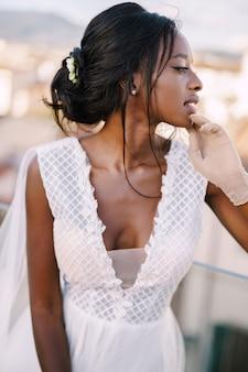 Mooie afrikaanse amerikaanse bruid in een witte trouwjurk, raakt haar gezicht in vintage handschoenen