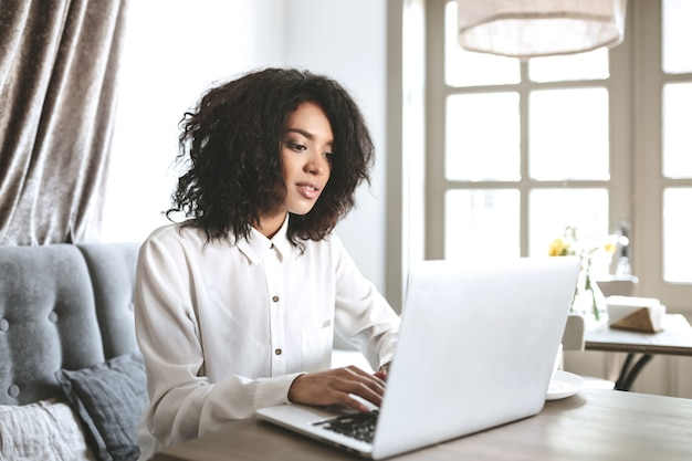Mooie afrikaanse amerikaanse meisjeszitting in restaurant met laptop. mooi meisje werkt op haar computer in café