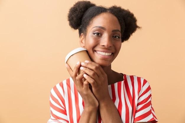Mooie afrikaanse amerikaanse vrouw die in vrijetijdskleding document kop met afhaalkoffie houdt, geïsoleerd