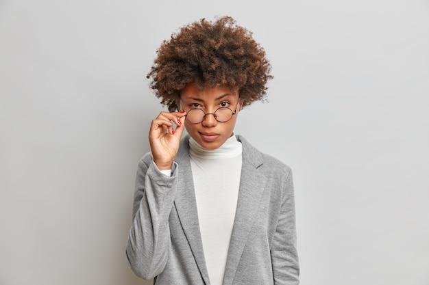Mooie afrikaanse amerikaanse vrouw kijkt aandachtig door een ronde bril
