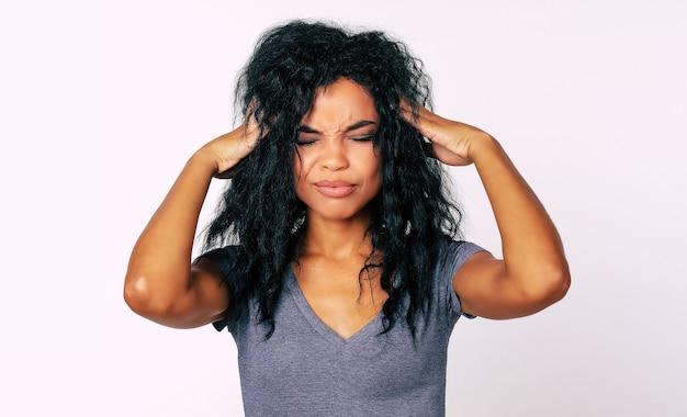 Mooie afrikaanse etnische vrouw in grijs t-shirt staat tegenover de camera met haar ogen dicht en haar vingers aanraken van de slapen als een teken van stress of hoofdpijn