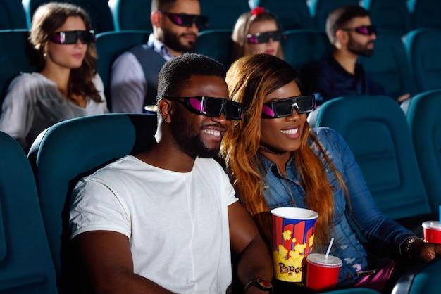 Mooie afrikaanse paar genieten van een film in de bioscoop lacht vrolijk