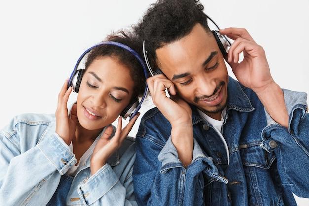 Mooie afrikaanse paar in denim shirts samen poseren terwijl het luisteren van muziek met gesloten ogen over grijze muur
