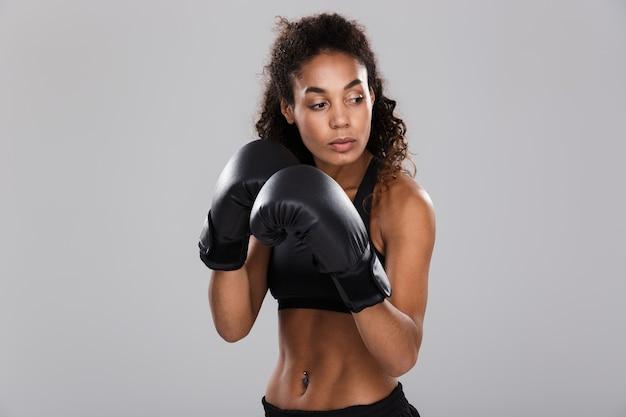 Mooie afrikaanse sportvrouw die over grijze achtergrond wordt geïsoleerd, die oefeningen met bokshandschoenen doet