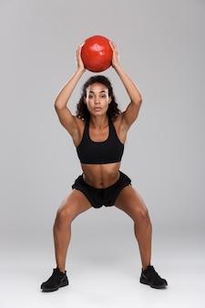 Mooie afrikaanse sportvrouw geïsoleerd over grijze achtergrond, oefeningen met een zware bal, gehurkt