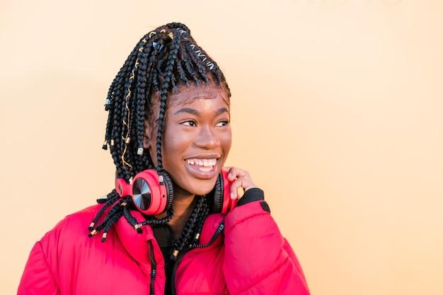 Mooie afrikaanse vrouw buitenshuis zwarte vrouw die naar muziek luistert met een koptelefoon