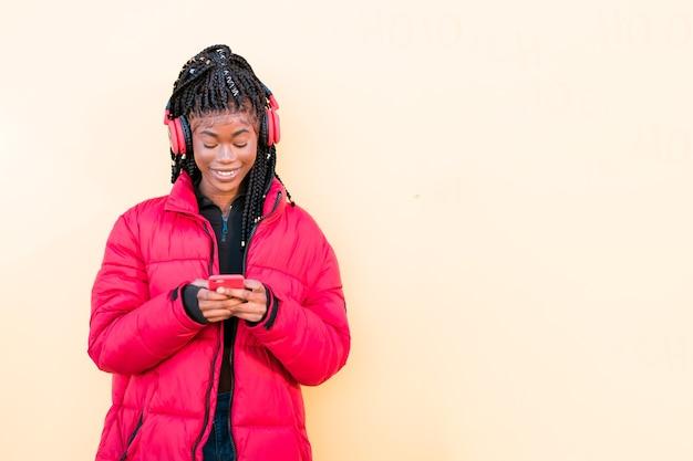 Mooie afrikaanse vrouw buitenshuis zwarte vrouw luistert naar muziek met een koptelefoon met smartphone