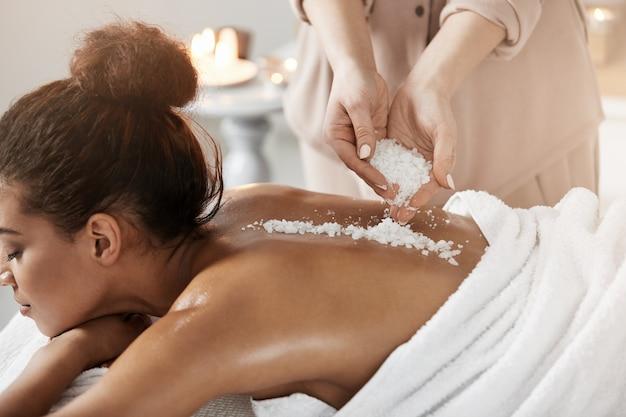 Mooie afrikaanse vrouw die genietend van de massage van de kuuroordgezondheid met overzees zout ontspannen.