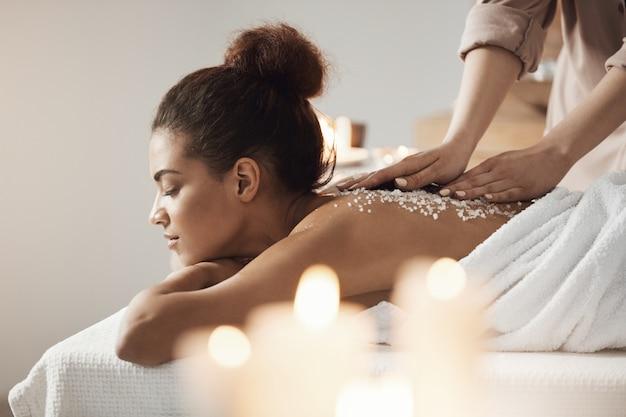 Mooie afrikaanse vrouw die genietend van de massage van de kuuroordgezondheid met overzees zout rusten.