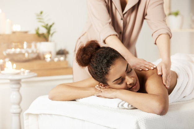 Mooie afrikaanse vrouw die genietend van massage met gesloten ogen in kuuroordsalon glimlachen.