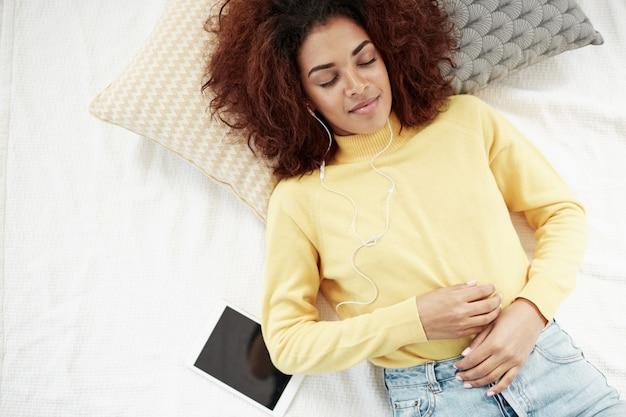 Mooie afrikaanse vrouw die in hoofdtelefoons aan muziek luistert die op bed ligt dat glimlacht met