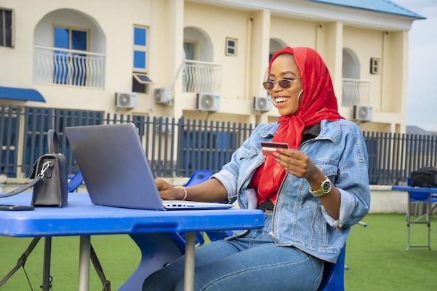 Mooie afrikaanse vrouw die lacht tijdens het gebruik van haar laptop en creditcard buiten.