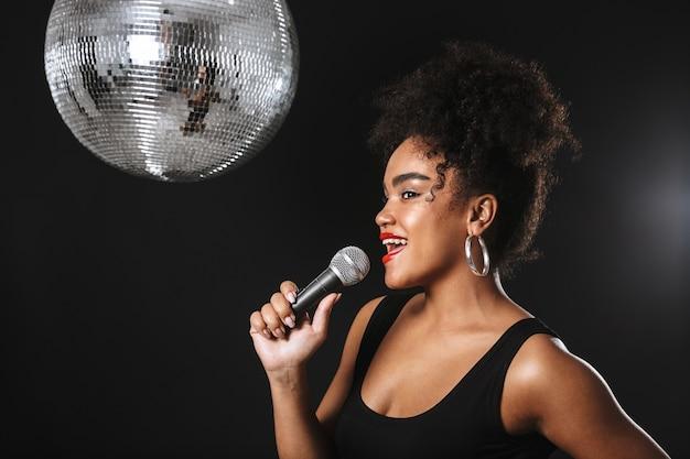 Mooie afrikaanse vrouw die zich met zilveren discobal bevindt die over zwarte ruimte wordt geïsoleerd, die microfoon houdt