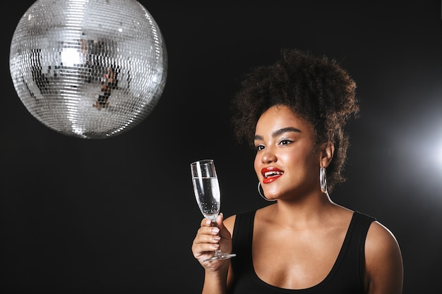 Mooie afrikaanse vrouw die zich met zilveren discobal bevindt die over zwarte ruimte wordt geïsoleerd