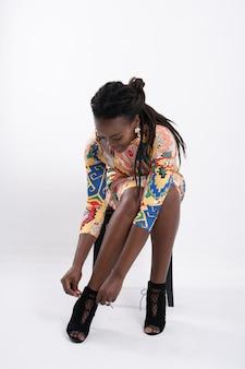 Mooie afrikaanse vrouw haar dreadlocks met een gelukkige houding, gekleed in een jurk met bloemmotief, zwarte schoenen met hoge hakken, oorbellen dragen volledige lengte lichaamsportret geïsoleerd op een witte achtergrond.