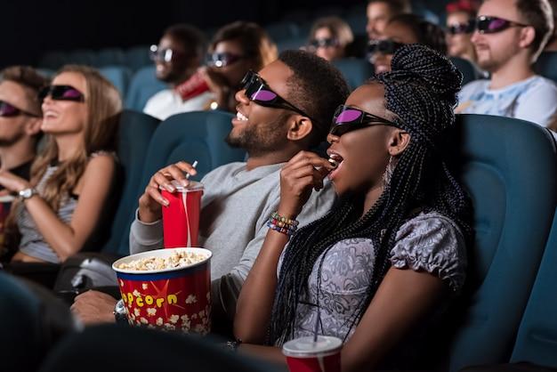 Mooie afrikaanse vrouw in 3d-bril eten popcorn terwijl op een date met haar vriend in de bioscoop