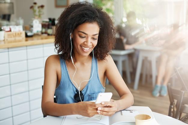 Mooie afrikaanse vrouw in hoofdtelefoons glimlachen die de zitting van het telefoonscherm bekijken die in koffie rusten.