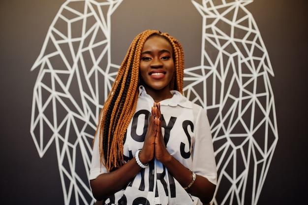 Mooie afrikaanse vrouw in modieuze vrijetijdskleding die tegen de muur van engelenvleugels stellen.