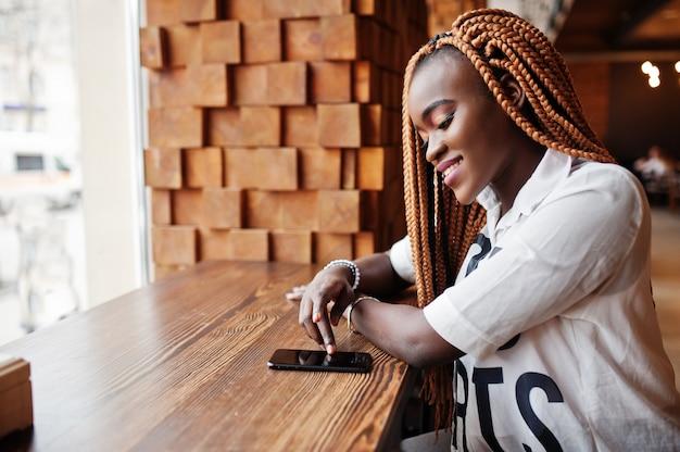Mooie afrikaanse vrouw in stijlvolle casual shirt en dreadlocks poseren in café in de buurt van de vensterbank en haar mobiele telefoon aan te raken.