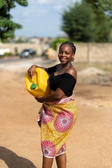 Mooie afrikaanse vrouw met een gele waterontvanger holding