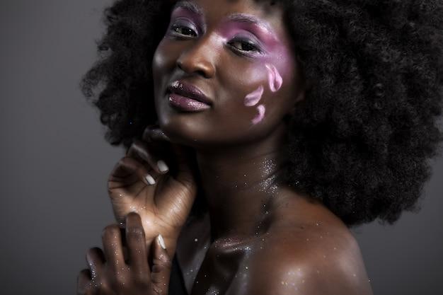 Mooie afrikaanse vrouw met grote krullende afro en bloemen in haar haar