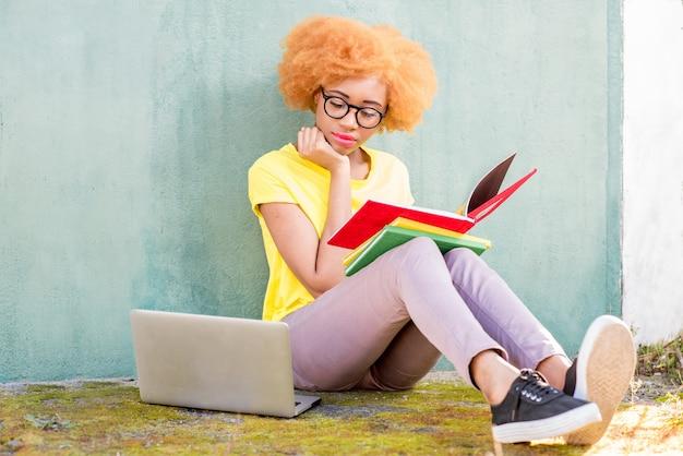 Mooie afrikaanse vrouw met krullend haar studeren met boeken en laptop buiten zitten op de groene muur achtergrond