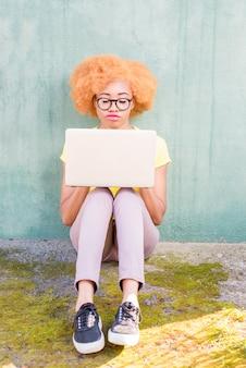 Mooie afrikaanse vrouw met krullend haar werken met laptop zittend op de groene muur achtergrond