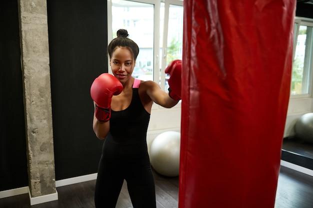 Mooie afrikaanse vrouwelijke atleet bokser met rode bokshandschoenen slaat op bokszak, kijkt naar de camera tijdens het uitvoeren van krijgskunst in de sportschool