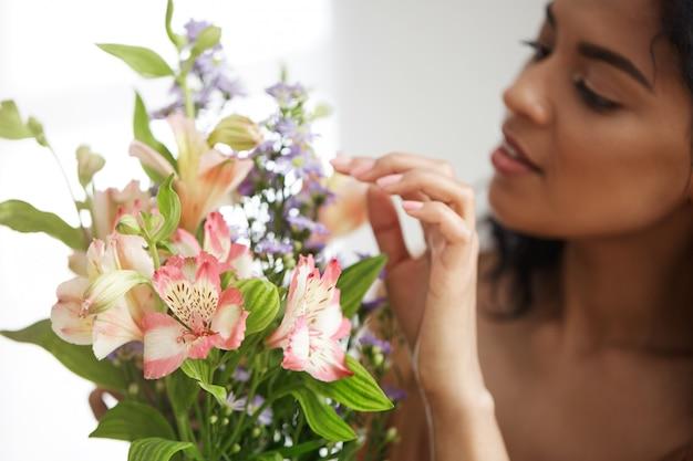 Mooie afrikaanse vrouwelijke bloemist die boeket van bloemen maakt. focus op alstroemeria's.