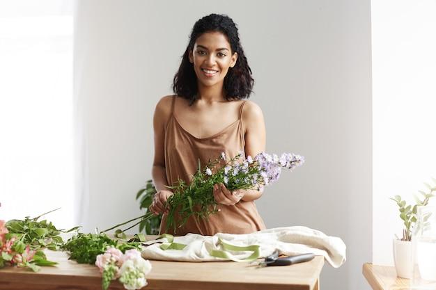 Mooie afrikaanse vrouwelijke bloemist die holdingsbloemen glimlacht. witte muur. bedrijfseigenaar blij om klanten te ontmoeten.