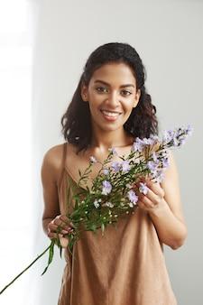 Mooie afrikaanse vrouwelijke bloemist die holdingsbloemen glimlacht. witte muur.