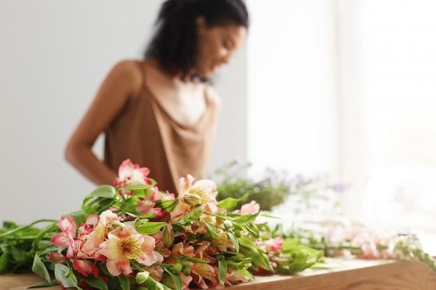 Mooie afrikaanse vrouwelijke bloemist werkende achtergrond. focus op alstroemeria's.