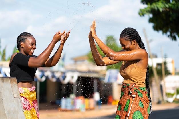 Mooie afrikaanse vrouwen die plezier hebben tijdens het halen van water