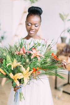 Mooie afro-amerikaanse bruid met tropische boeket in studio