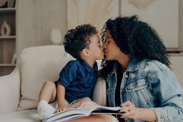 Mooie afro-amerikaanse familiemoeder met zoontje die elkaar kussen en liefde uiten terwijl ze samen thuis tijd doorbrengen, een boek lezen terwijl ze op een zachte witte bank in de woonkamer zitten