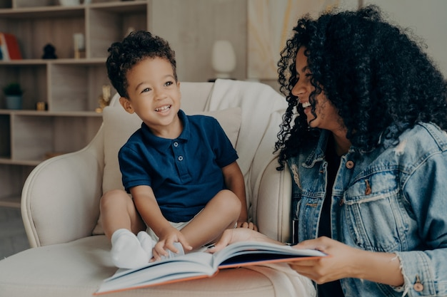 Mooie afro-amerikaanse moeder die een boek leest aan haar zoontje en lacht