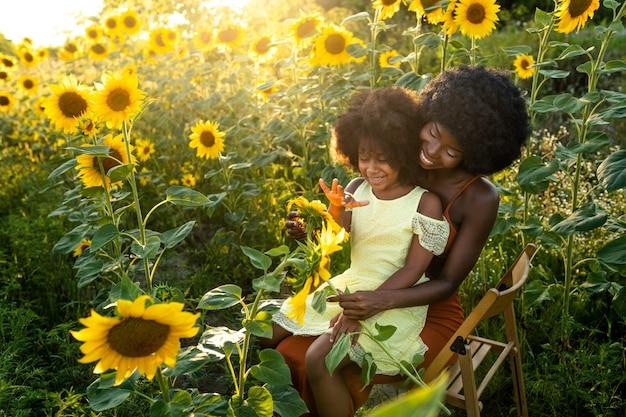 Mooie afro-amerikaanse moeder en dochter die spelen en plezier hebben in een zonnebloemveld