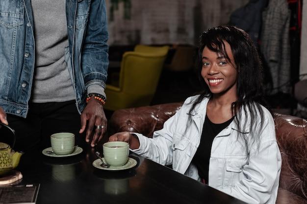 Mooie afro-amerikaanse vrouw die middelgroot schot glimlacht