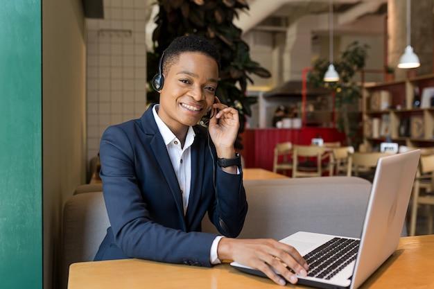 Mooie afro-amerikaanse vrouw die naar de camera kijkt en glimlacht, werkt in een coworking-café, videocommunicatie met behulp van headset zakenvrouw freelancer